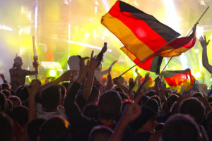 Berlin, Germany - July 13, 2014: Germany wins FIFA World Cup 2014, crowd of people gathering at Brandeburger Tor in Berlin for partying, getting crazy and supporting their team. A night of joy and happiness, with flags, music, lights and ecstatic crowd.